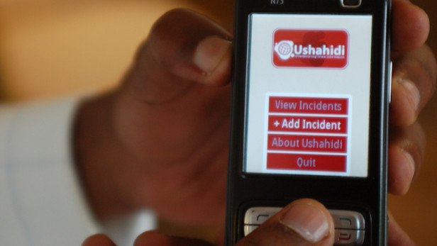 A phone screen shows the Ushahidi app. A pioneer in the use of technology to gather data and prevent conflict, Ushahidi was born out of the post-election conflict in Kenya in 2008. Photo by: Erik Hersman / CC BY